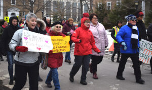group of women marching on street in Antigonish carrying placards in support of women's rights